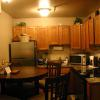 Fully-equipped kitchen with large refrigerator with ice maker, range, microwave, dishwasher, toaster, blender, coffee maker, and seating for up to four people.